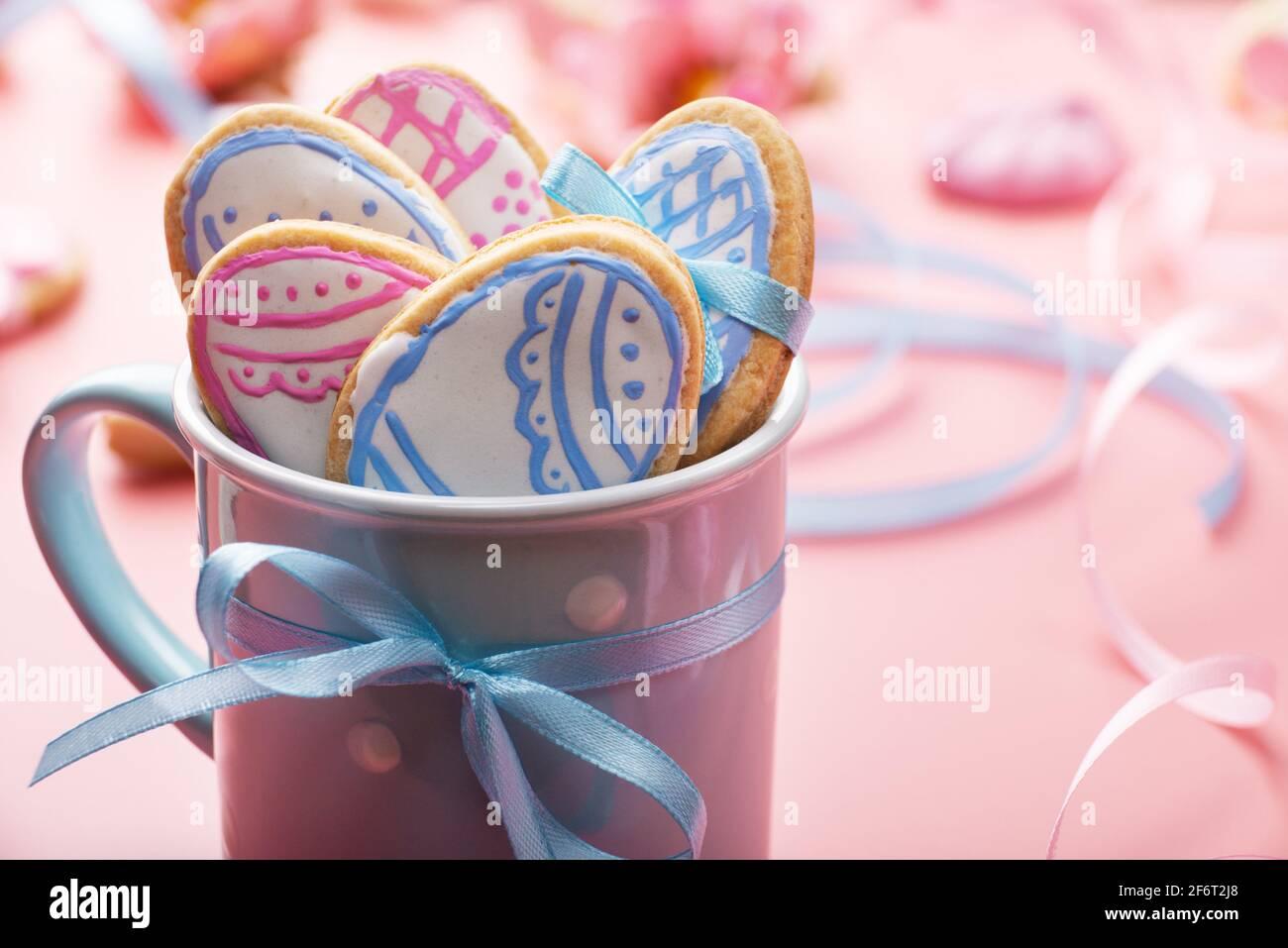 Fond de cuisson de Pâques de biscuits givrés en forme d'oeuf dans une tasse bleue sur fond rose. Banque D'Images