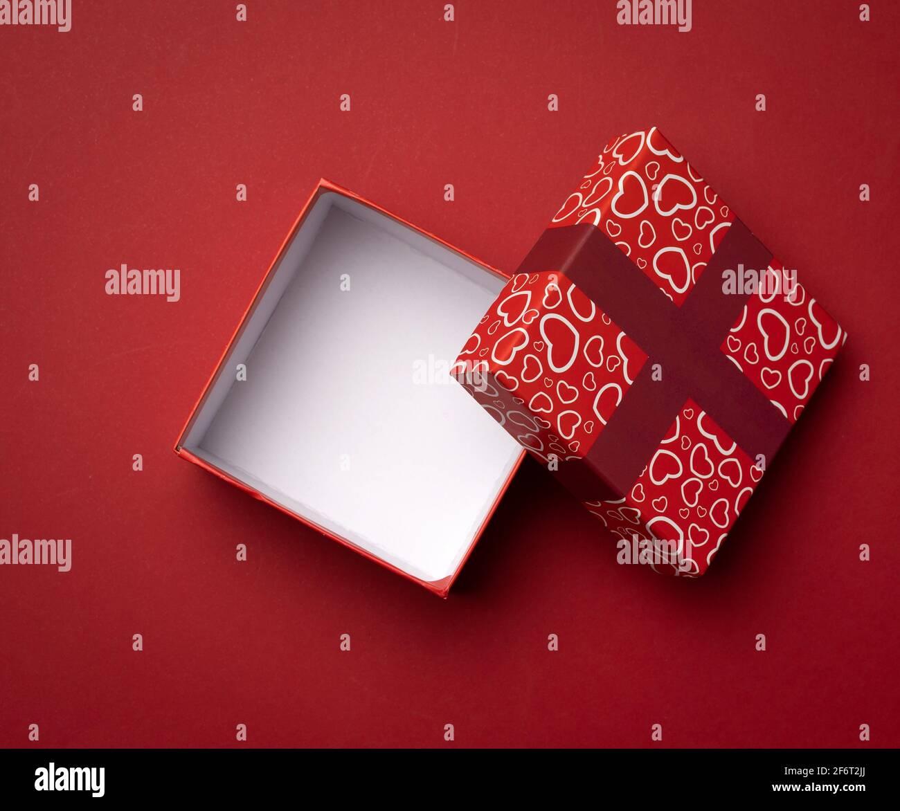 boîte rouge carrée vide sur fond rouge, cadeau ouvert, vue du dessus. Banque D'Images
