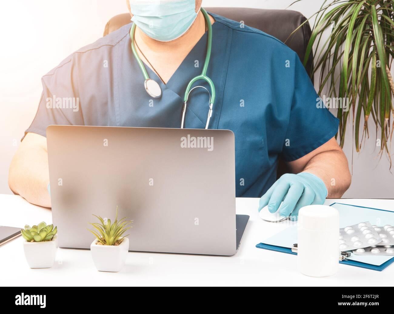 homme médecin assis à une table blanche en uniforme bleu et gants en latex, spécialiste travaille sur un ordinateur portable, concept de télémaintenance, thérapeute Banque D'Images
