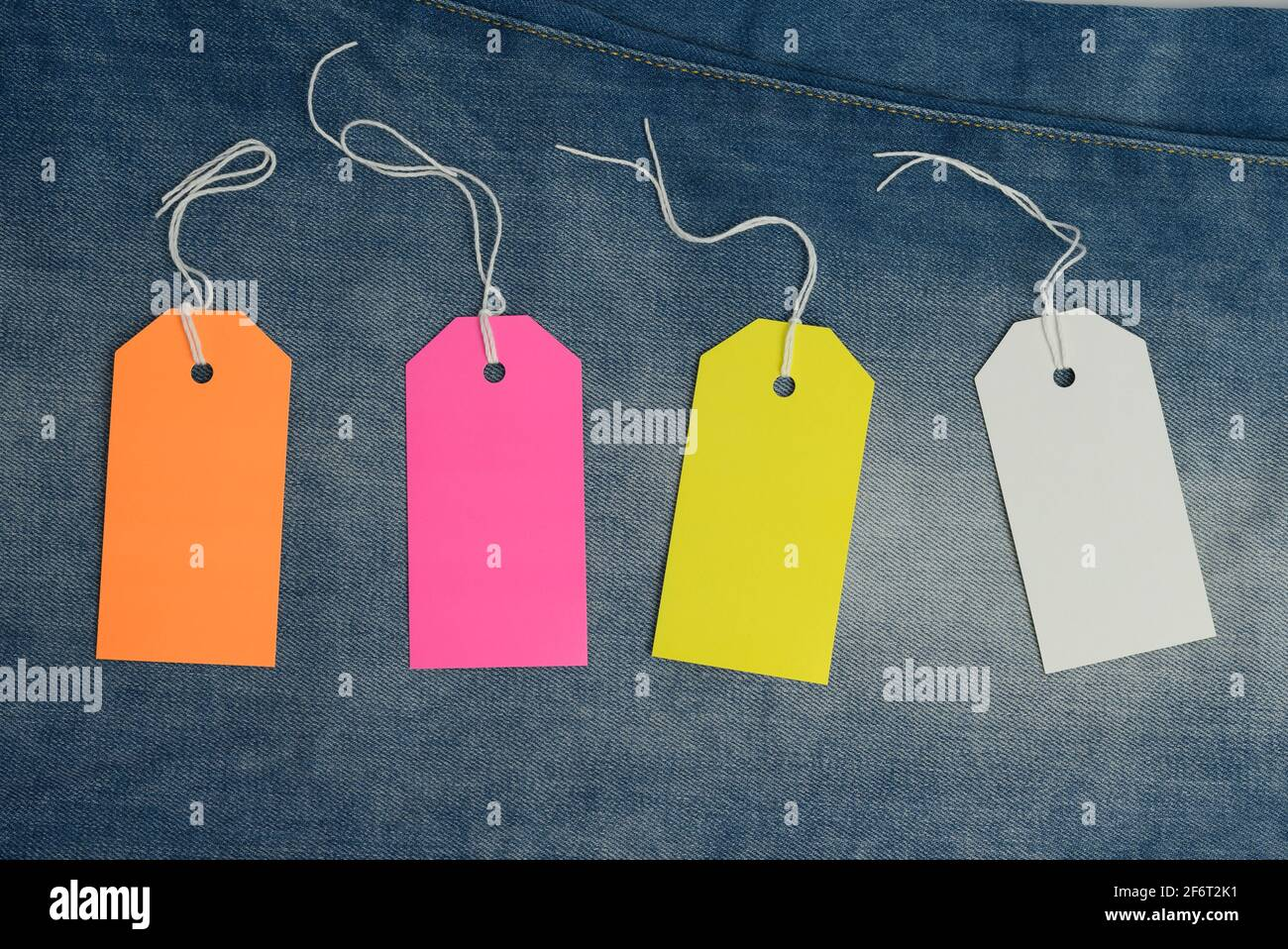 étiquettes en carton rectangulaires vierges de couleur sur fond bleu jean, vue du dessus. Banque D'Images