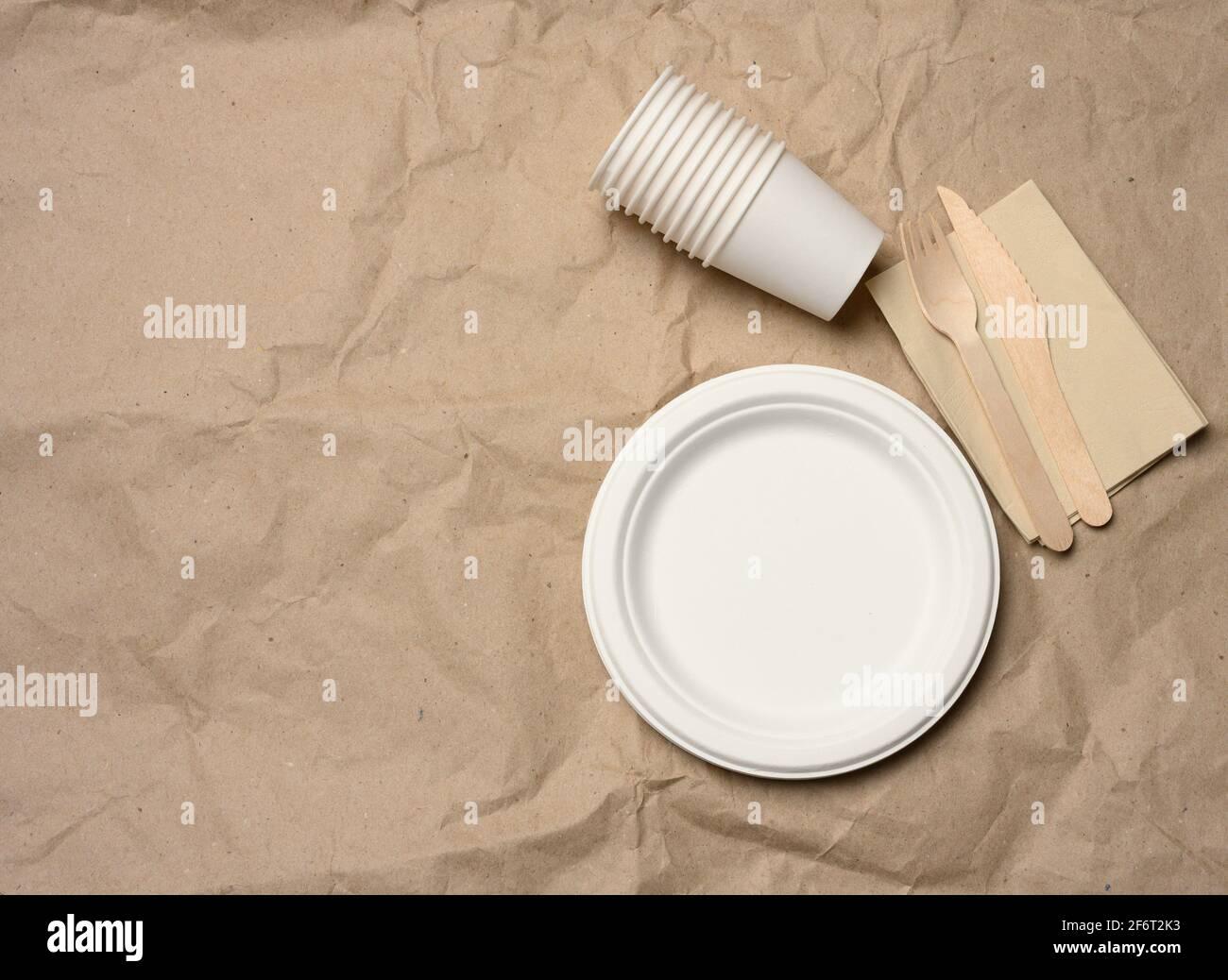 assiettes et tasses en papier blanc rondes jetables sur fond de papier marron, vue de dessus, zéro déchet. Banque D'Images