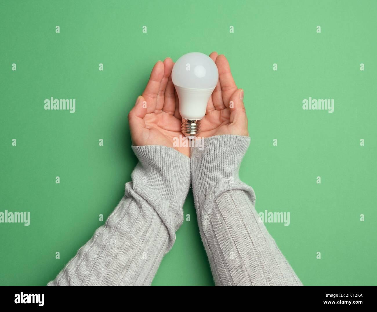 lampe en verre blanc à main femelle, énergie verte, vue de dessus. Banque D'Images