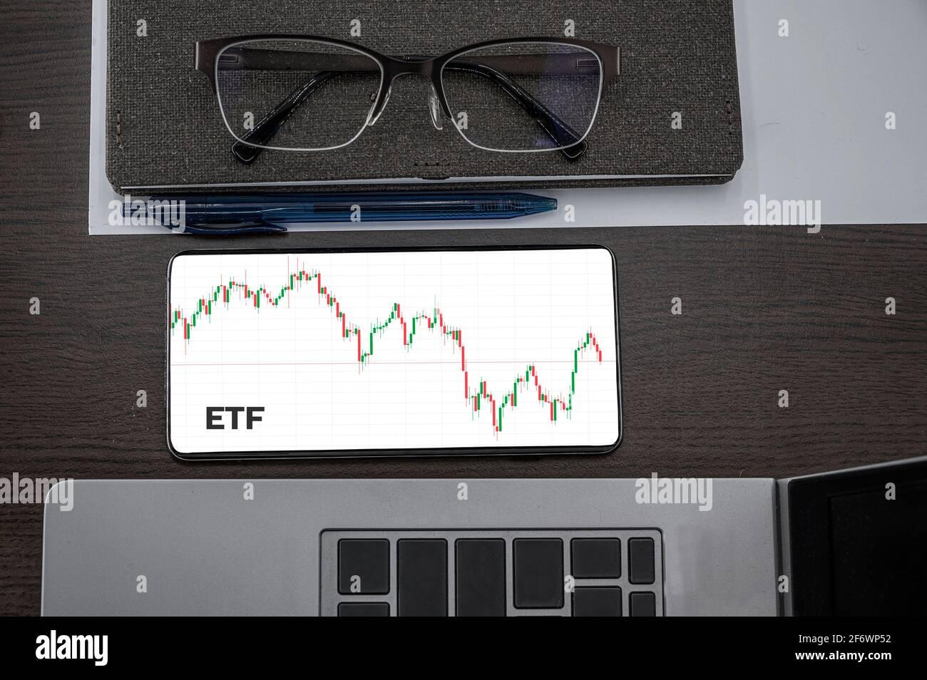 Acheter ou vendre le concept ETF. Fonds échangé. Vue de dessus du tableau de chandeliers de prix des actions dans le téléphone sur la table près de l'ordinateur portable, bloc-notes et lunettes avec insc Banque D'Images