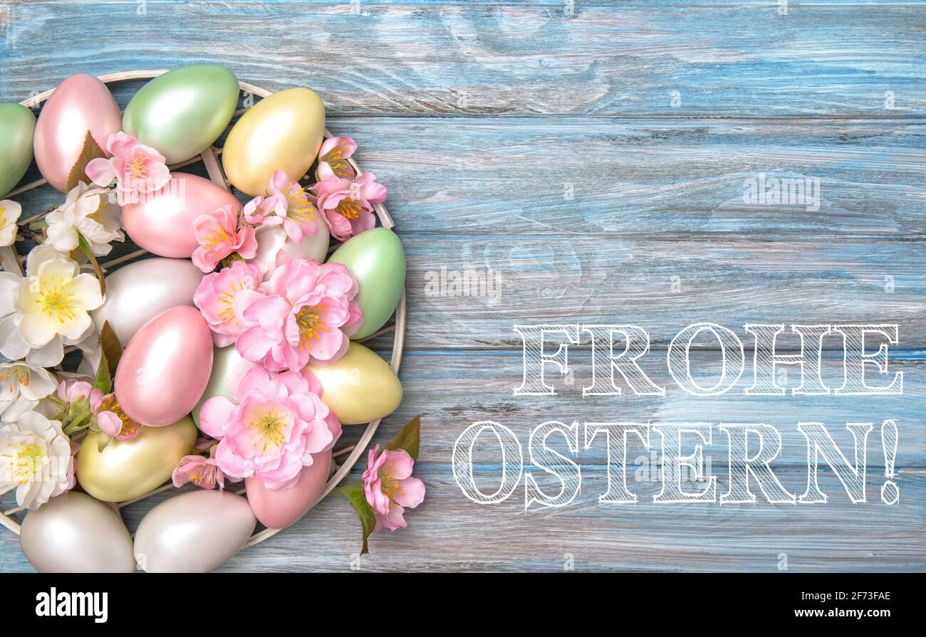 Décoration oeufs de Pâques avec fleurs de printemps. Joyeuses Pâques en allemand Banque D'Images