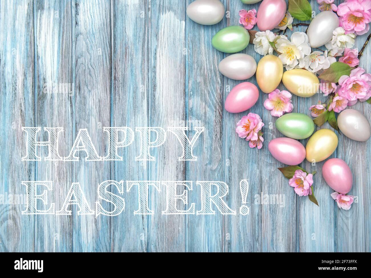 Joyeuses Pâques ! Œufs de Pâques et fleurs de printemps sur fond bleu en bois Banque D'Images