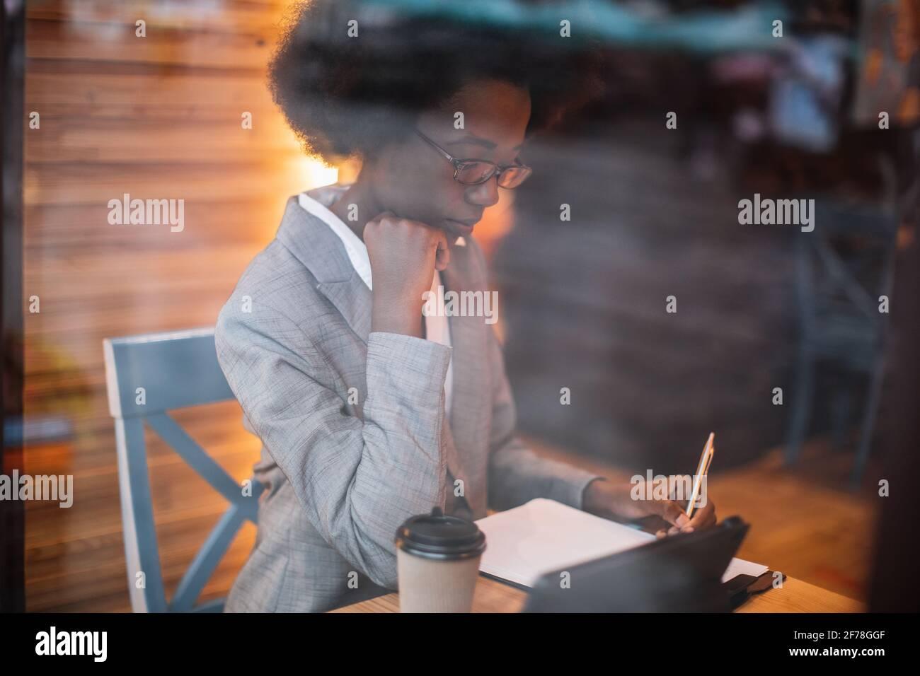 Jeune femme africaine concentrée en costume d'affaires écrivant des notes tout en étant assise à table de café avec une tablette numérique. Concept de travail à distance, personnel et technologie. Banque D'Images