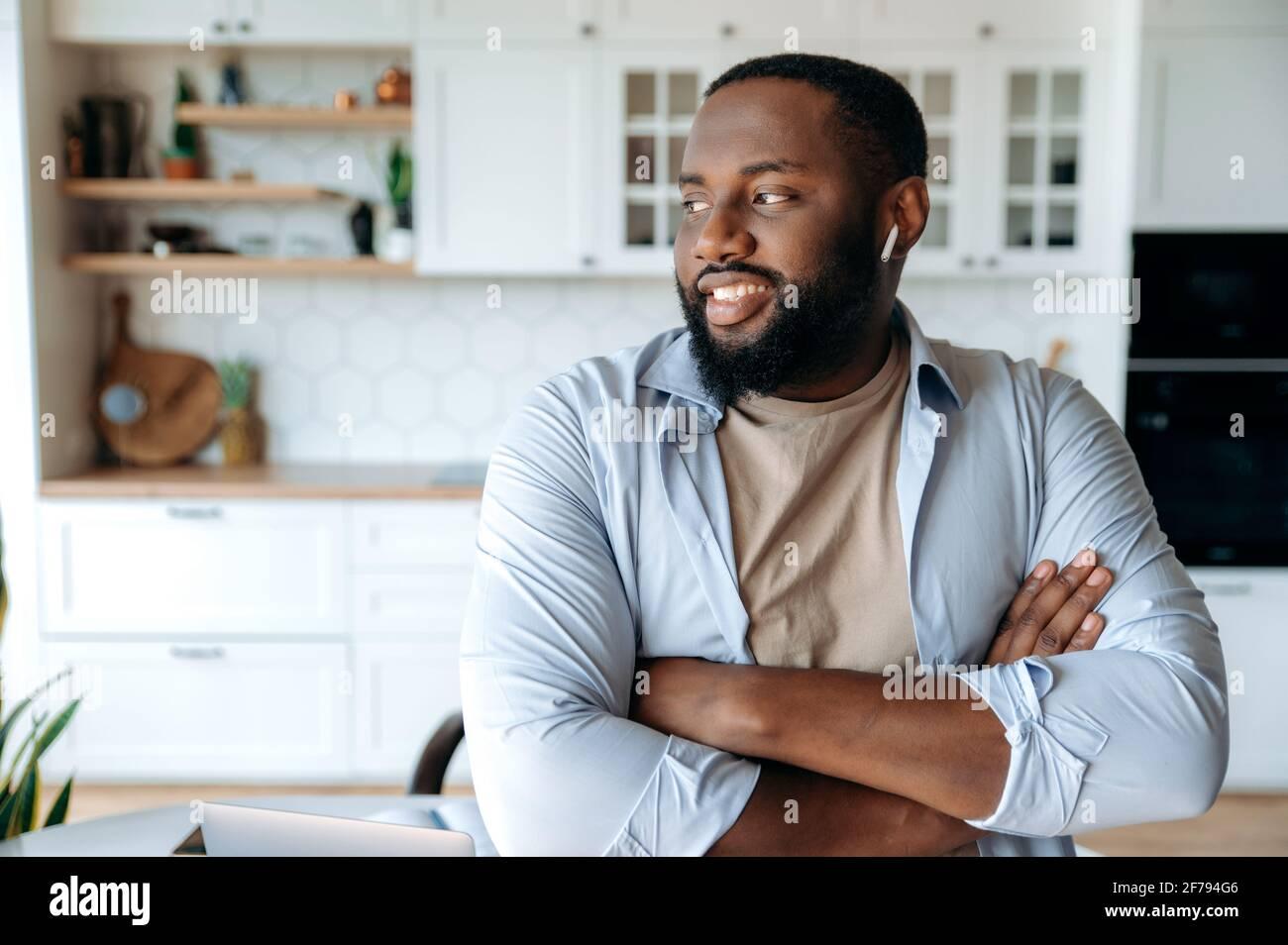 Portrait d'un jeune homme afro-américain plein de joie et confiant avec une barbe portant un casque debout dans le salon, portant des vêtements élégants, regardant sur le côté, bras croisés devant lui, souriant Banque D'Images