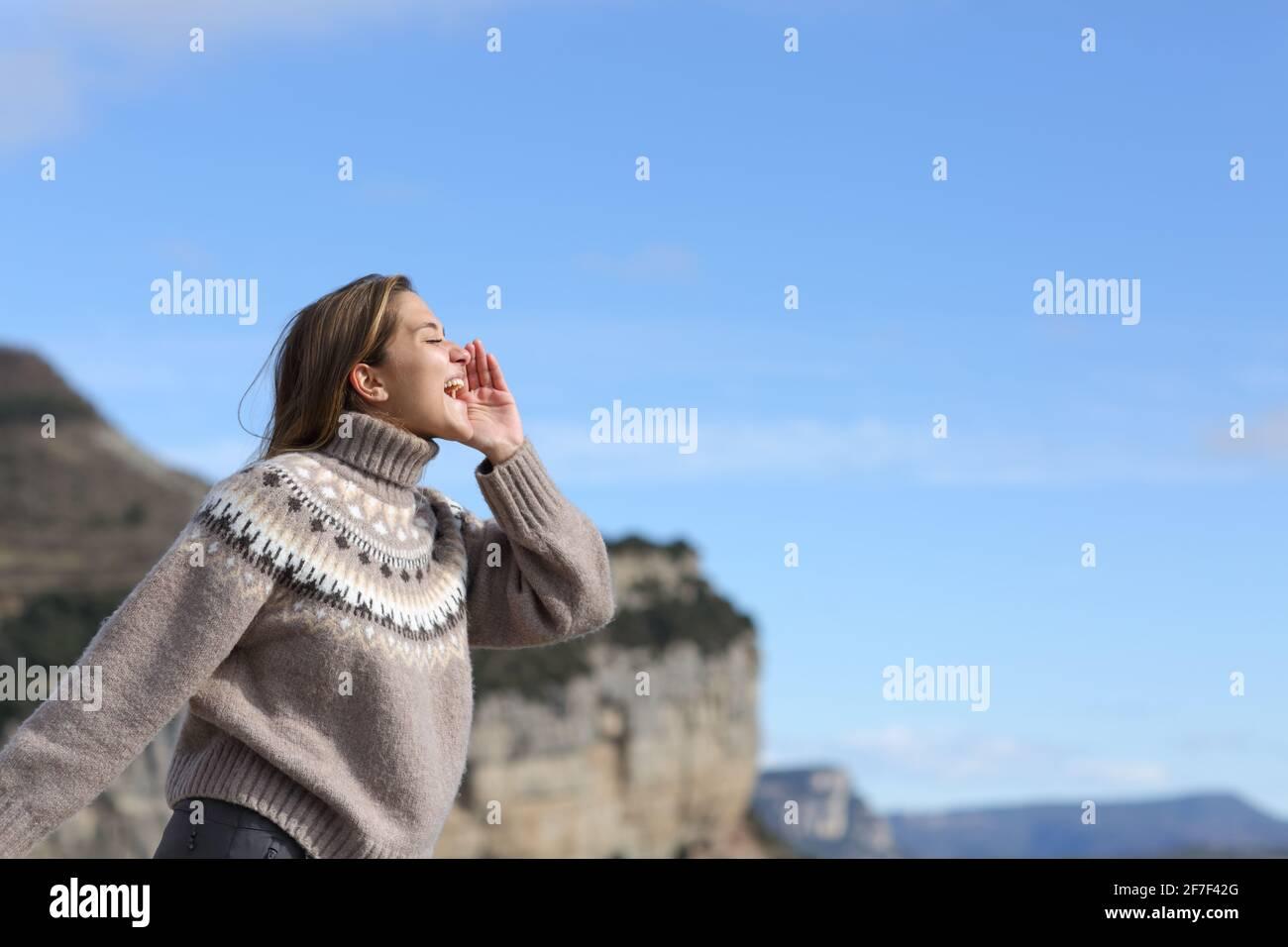 Vue latérale d'une femme heureuse criant pour l'écho en montagne en hiver Banque D'Images