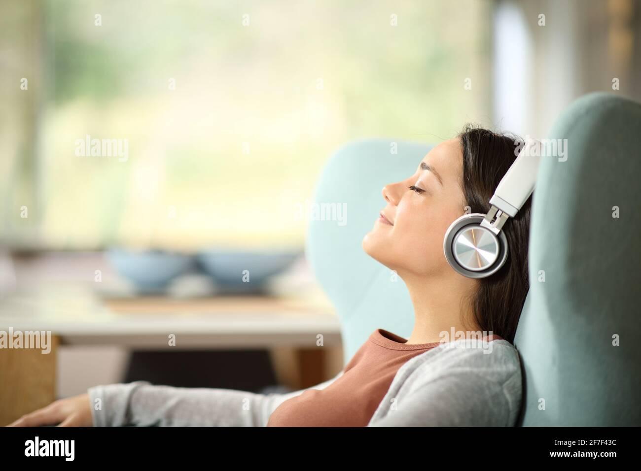 Portrait d'une femme décontractée portant un casque sans fil en vue latérale écouter de la musique sur une chaise à oreilles Banque D'Images