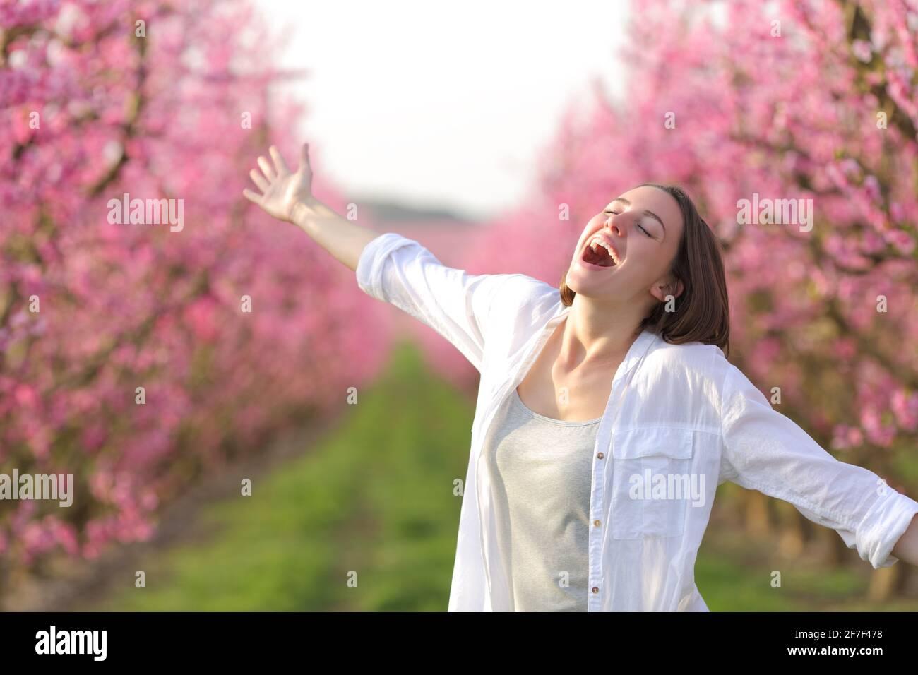 Femme excitée s'étirant les bras célébrant le printemps et les vacances dans un champ fleuri rose Banque D'Images