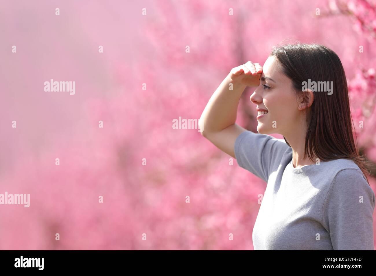 Vue latérale d'une femme heureuse cherchant à regarder loin protéger du soleil avec sa main dans un rose fleuri champ Banque D'Images