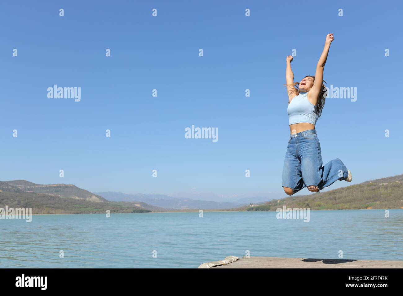 Bonne femme sautant en vacances dans un lac l'été vacances Banque D'Images