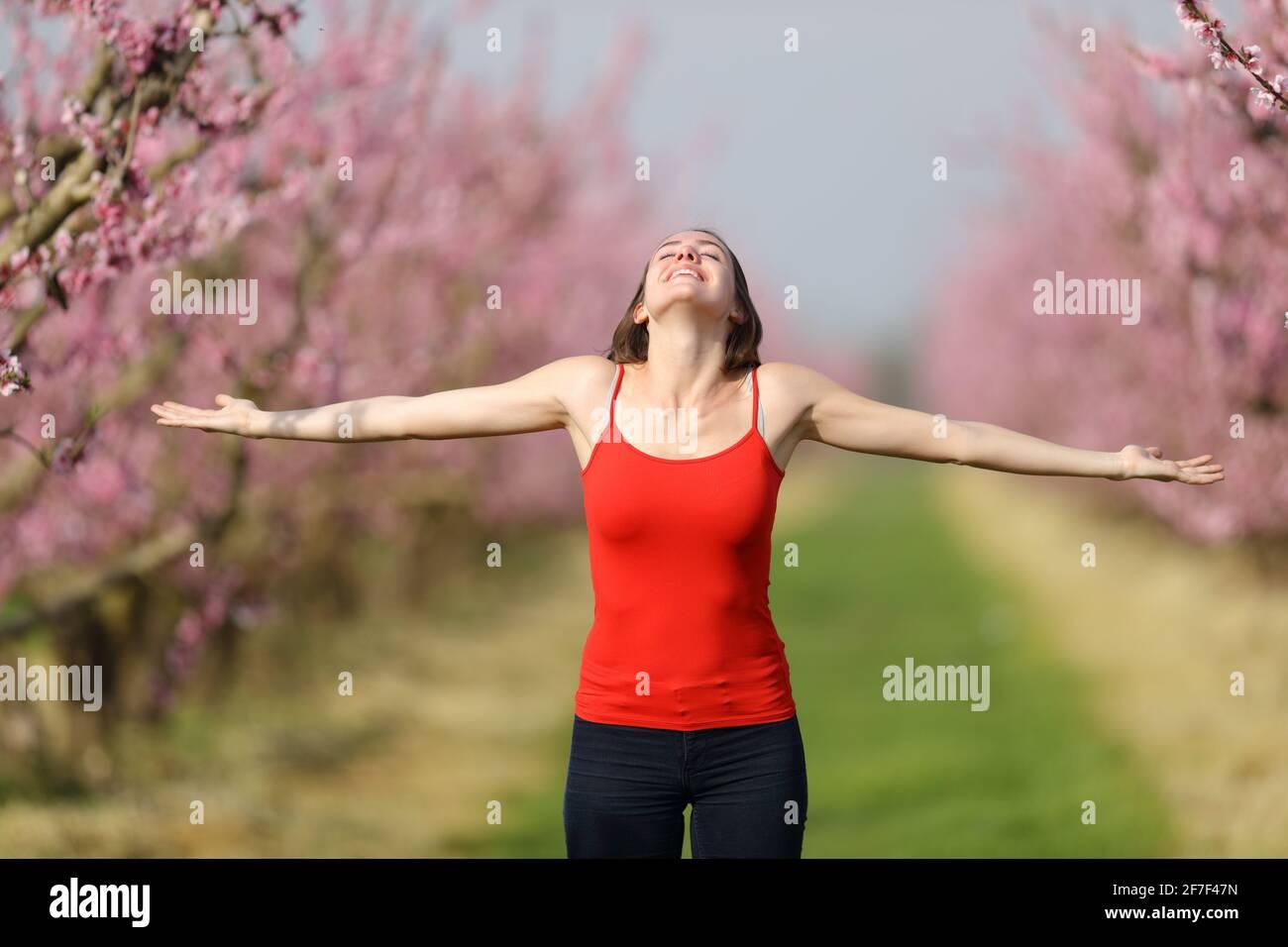 Portrait d'une femme excitée célébrant les étirements du printemps bras dans un champ fleuri Banque D'Images