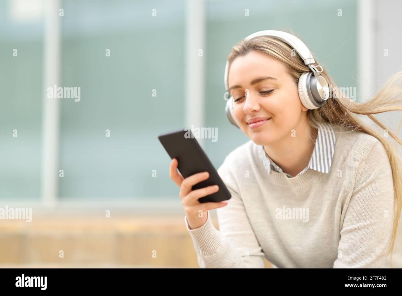 Un adolescent satisfait écoute de la musique sur un smartphone assis la rue Banque D'Images