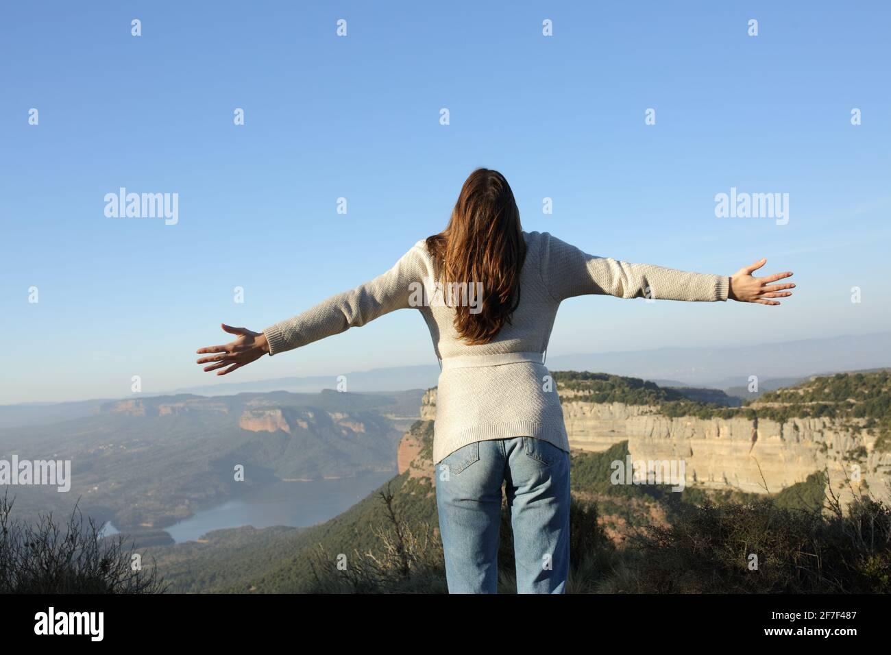 Vue arrière d'une femme célébrant la propagation de vacances avec ouvert bras dans la montagne Banque D'Images