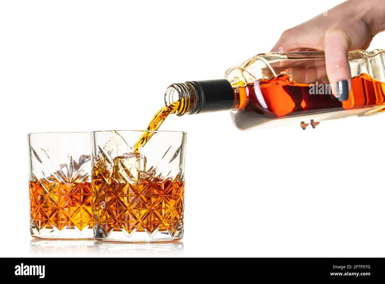 le whisky est versé dans un verre de la bouteille sur blanc arrière-plan isolé Banque D'Images