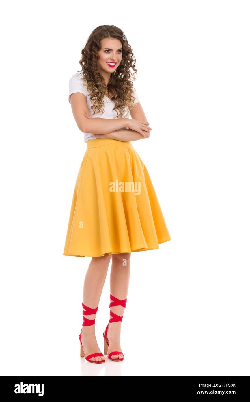 Belle jeune femme en jupe jaune, blanc haut et rouge talons hauts est debout avec les bras croisés, regardant loin et souriant. Plein studio tourné i Banque D'Images
