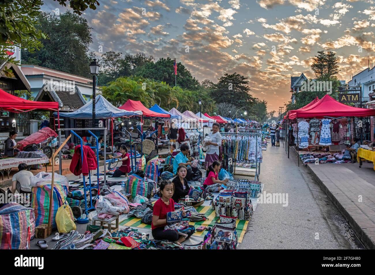 Marché de nuit avec étals vendant des vêtements colorés, du textile et des souvenirs dans la ville de Luang Phabang / Luang Prabang / Louangphabang, Laos Banque D'Images