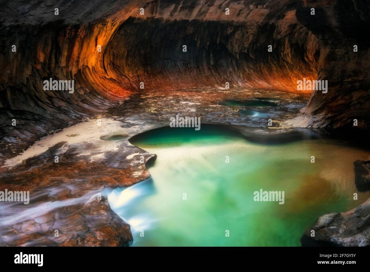 Une lumière réfléchissante illumine les parois du canyon de la fente en labyrinthe du Subway avec ses piscines émeraude dans le parc national de Zion. Banque D'Images