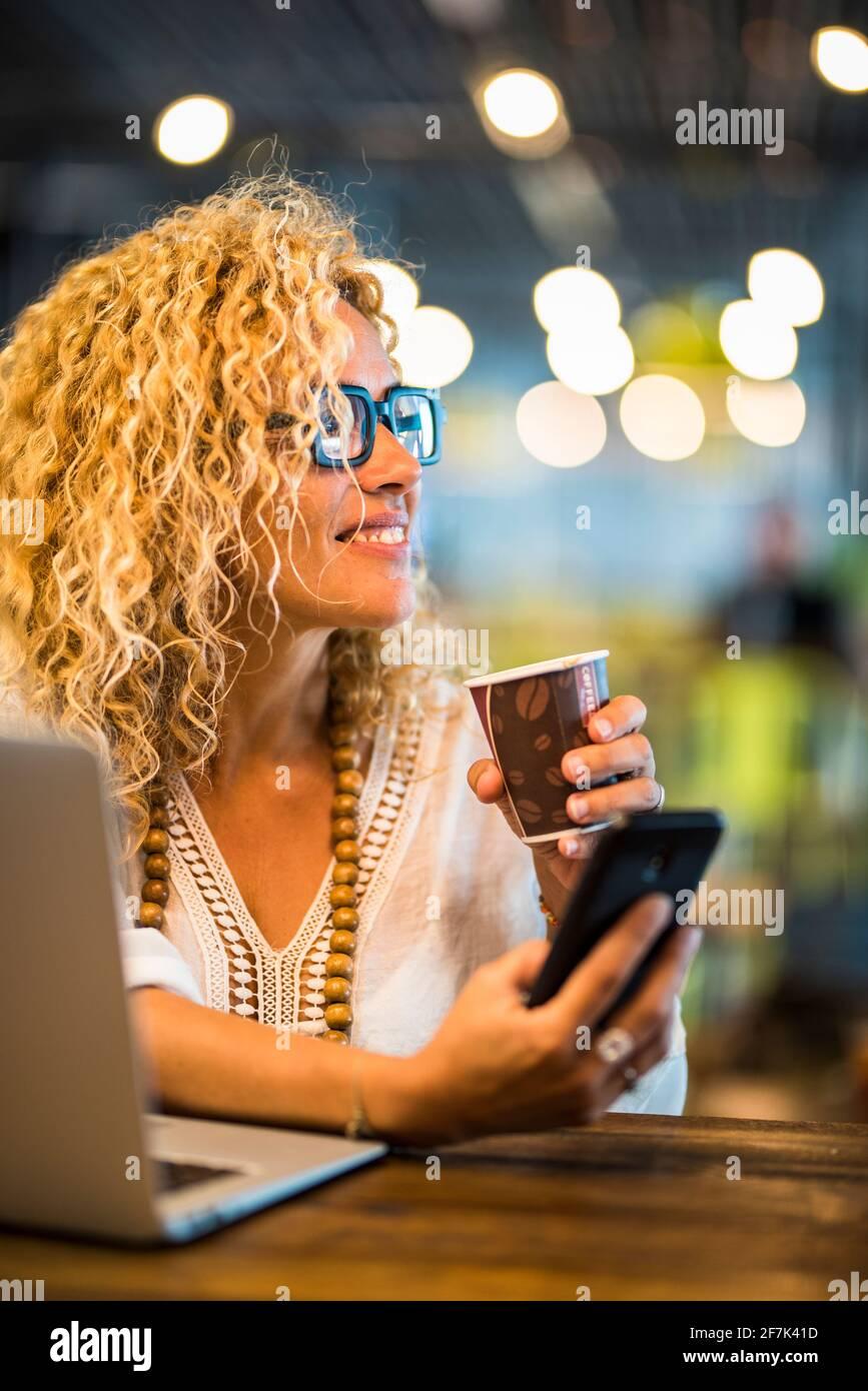 Travail de voyage et concept de travail intelligent style de vie avec jeune adulte jolie femme utiliser le téléphone et ordinateur de bureau avec connexion d'itinérance et accès à internet sans fil gratuit Banque D'Images