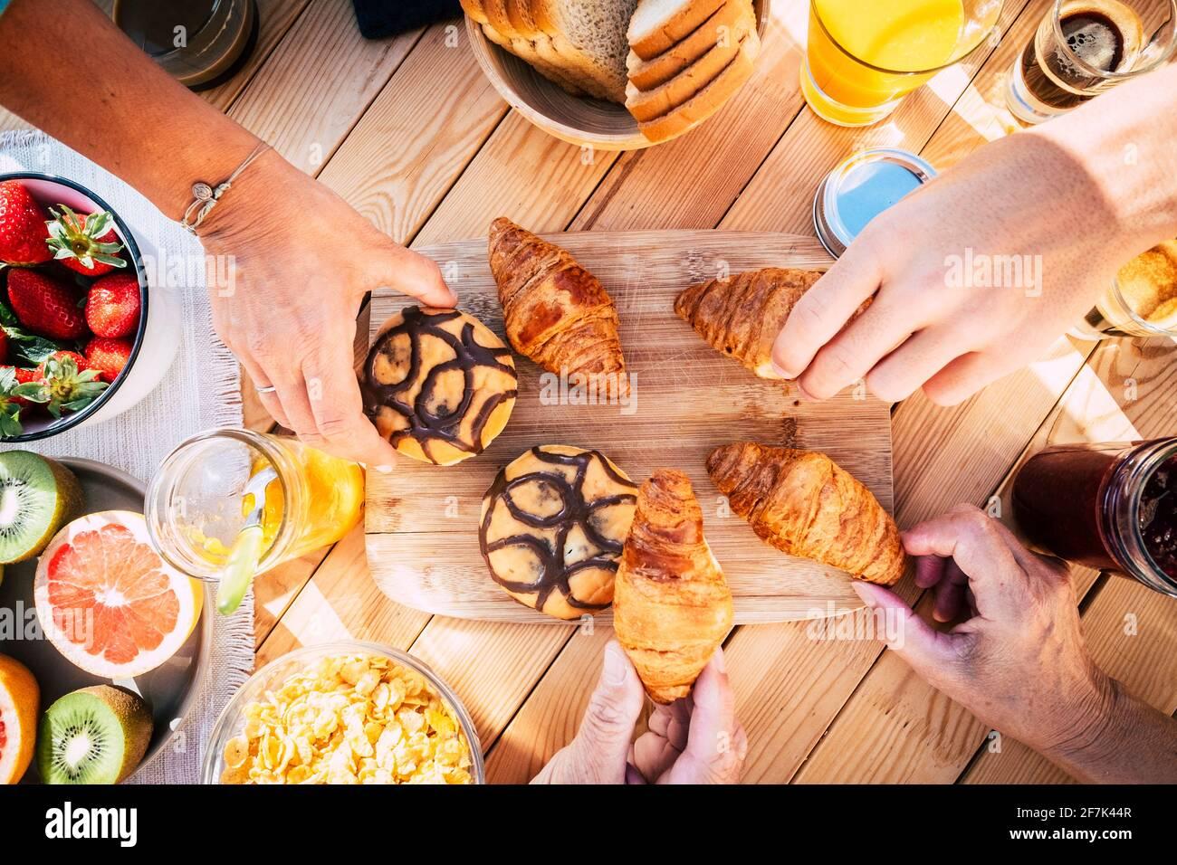 Vue de dessus de la table avec la nourriture du petit déjeuner et les personnes qui mangent ensemble dans l'amitié - heure du matin en famille et boulangerie fraîche croissant - vue rapprochée des mains pi Banque D'Images