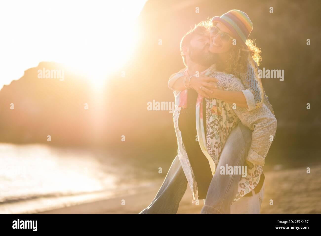 Couple caucasien adulte s'amuser ensemble dans le pigegyback - homme porter la femme et rire beaucoup avec l'amour et le bonheur à la plage avec coucher de soleil lumière incroyable Banque D'Images
