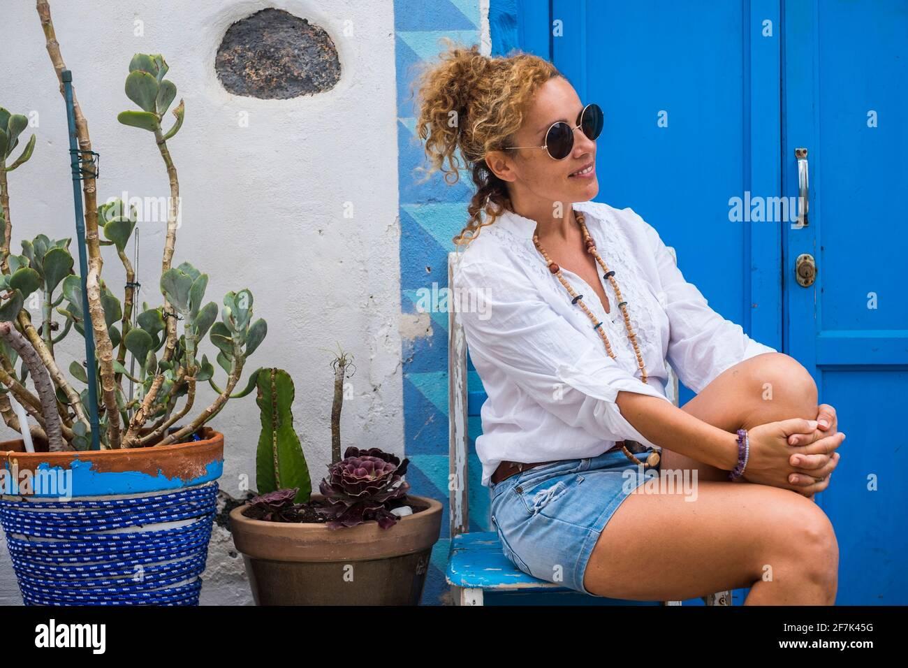 Belle femme s'asseoir à l'extérieur de la maison et se détendre - à la mode femmes en détente activités de loisirs en plein air avec porte bleue et maison en arrière-plan Banque D'Images