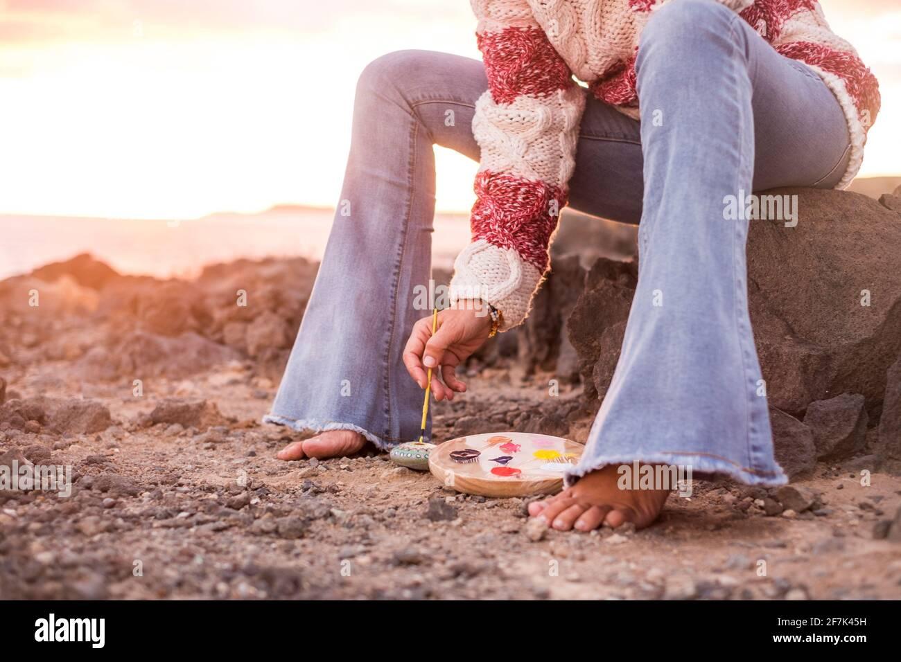Personnes méconnaissables femme assise à l'extérieur dans la nature paimant un pierre - concept d'activités de loisirs artistiques en plein air et de liberté - couleurs et a Banque D'Images