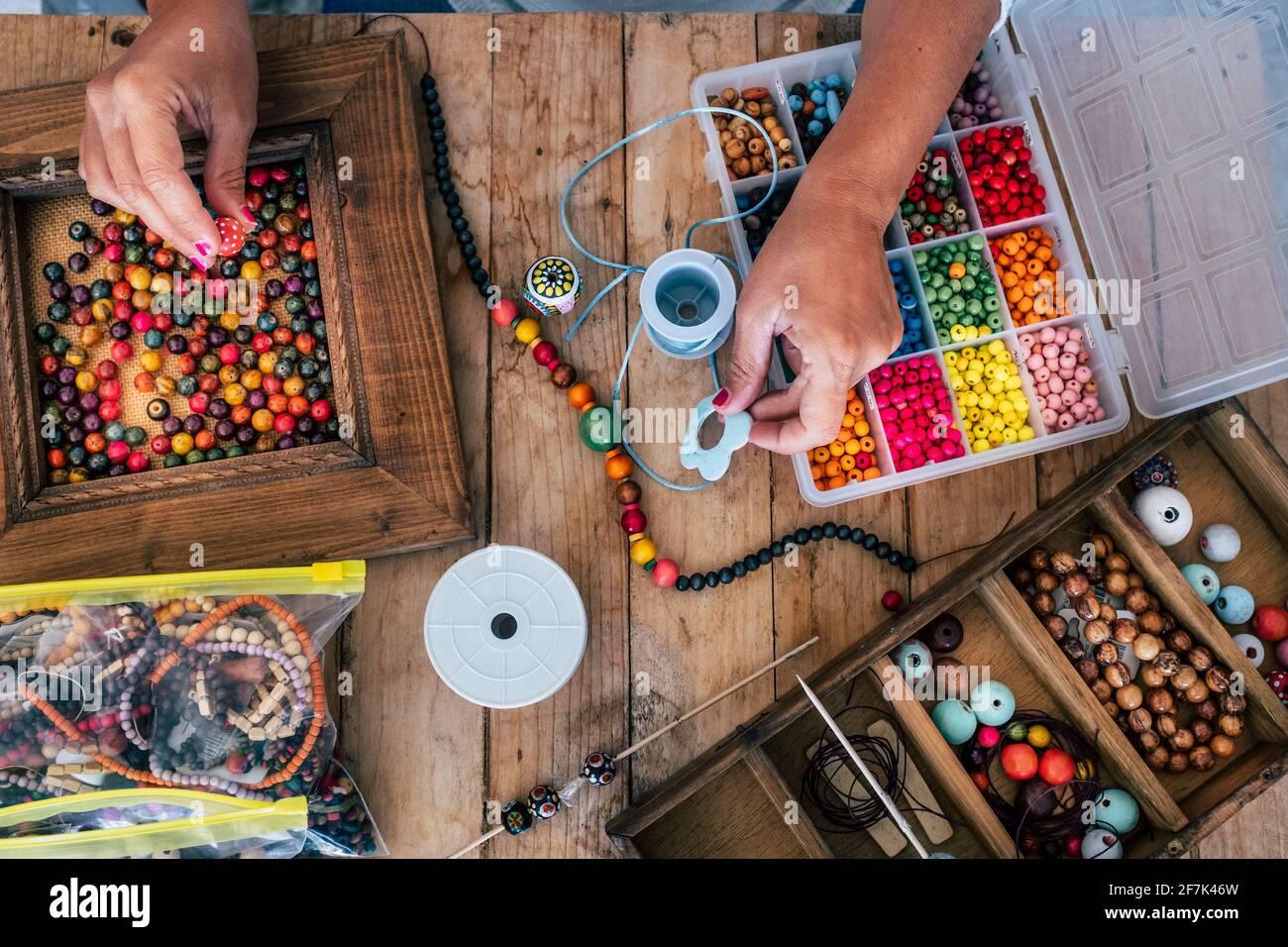 Fabrication de bijoux faits à la main. Boîte avec perles sur une ancienne table en bois. Vue de dessus avec les mains de femme - tutoriel pour apprendre à faire des bracelets et des bijoux sur Banque D'Images