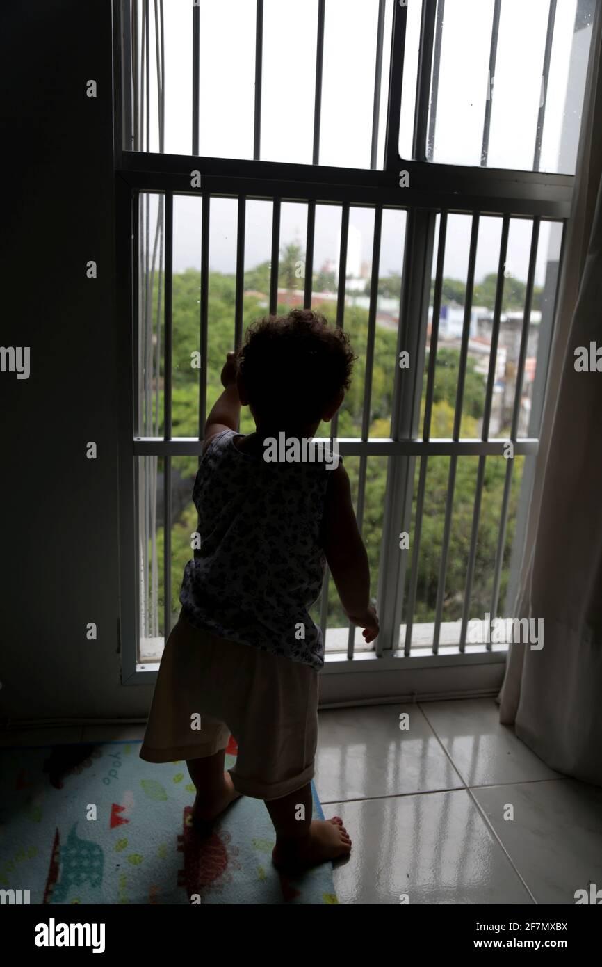 salvador, bahia / brésil - 14 octobre 2014: L'enfant est vu par une fenêtre avec une grille dans un appartement dans le quartier de Cabula dans la ville de Salv Banque D'Images