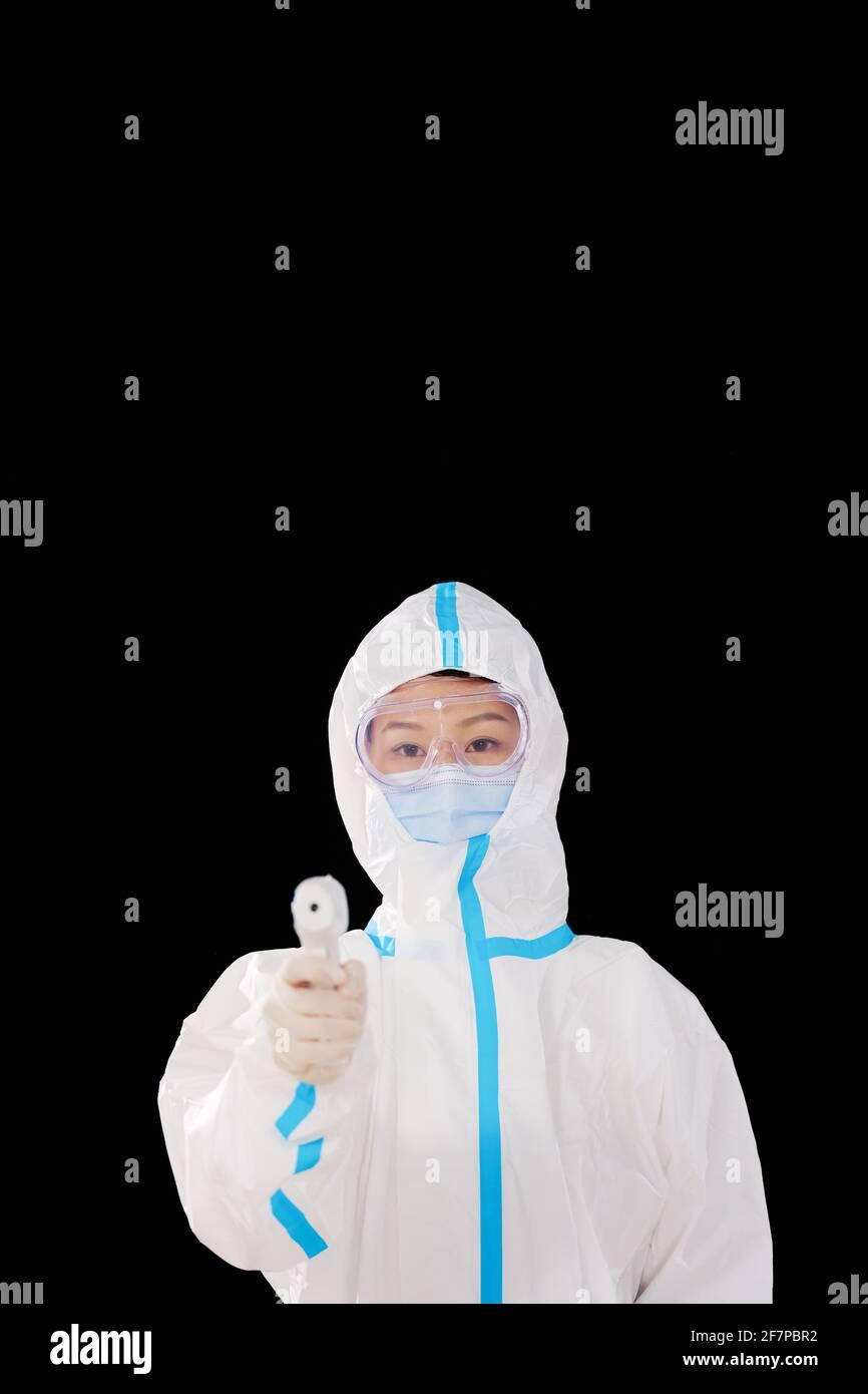 Une femme médecin en vêtements de protection médicale prend de la température Banque D'Images