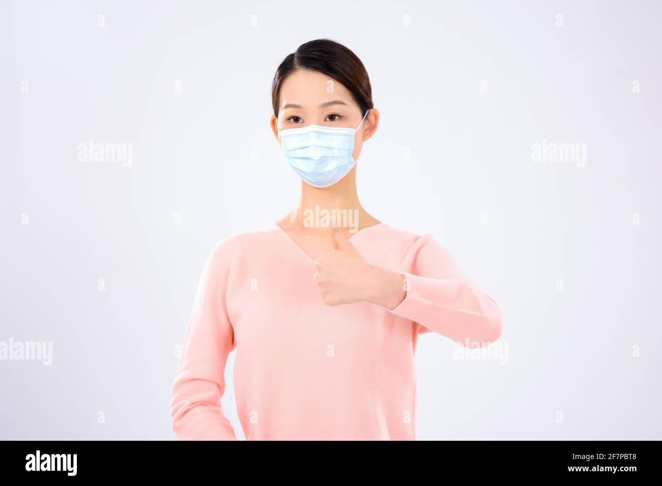 Une jeune femme avec un masque a tenu son pouce vue avant Banque D'Images