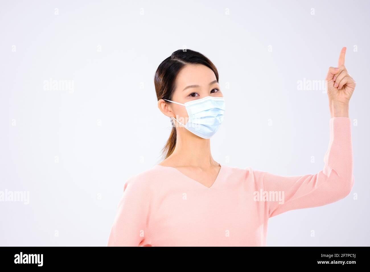 Une jeune femme avec un masque pointant vers le haut Banque D'Images