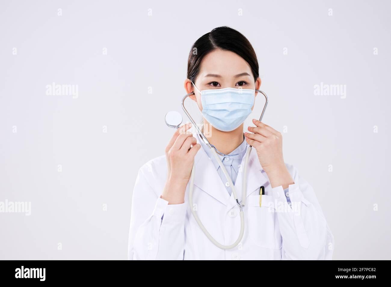 Une femme médecin a mis sur un stéthoscope regardant le appareil photo Banque D'Images