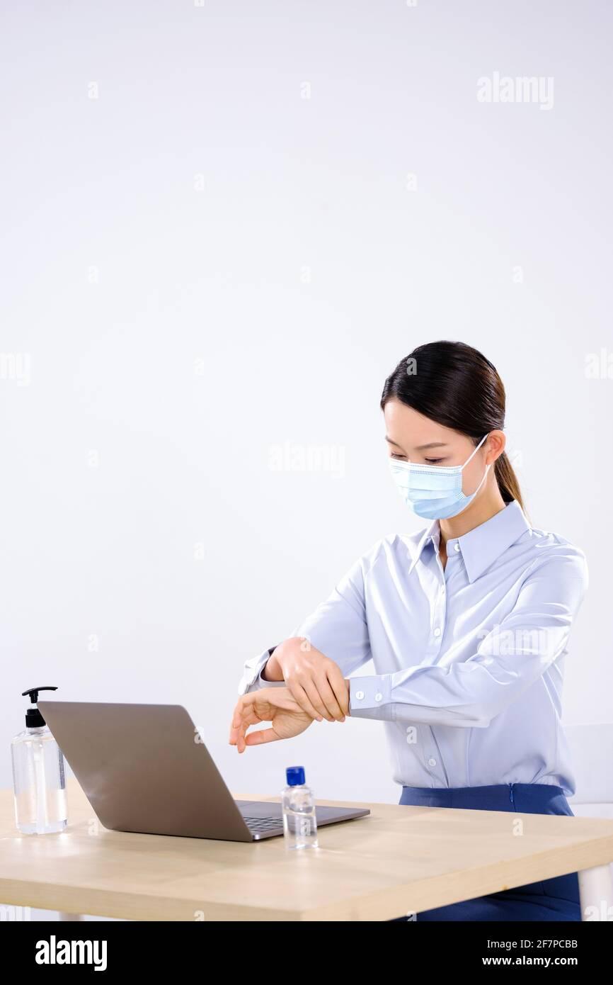 Une femme d'affaires portant un masque utilise un côté désinfectant pour les mains vue Banque D'Images