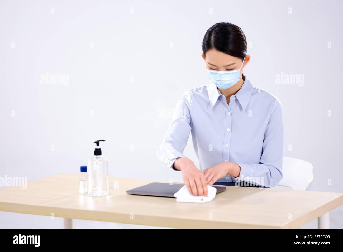 Une femme d'affaires portant un masque essuie son ordinateur avec alcool Banque D'Images