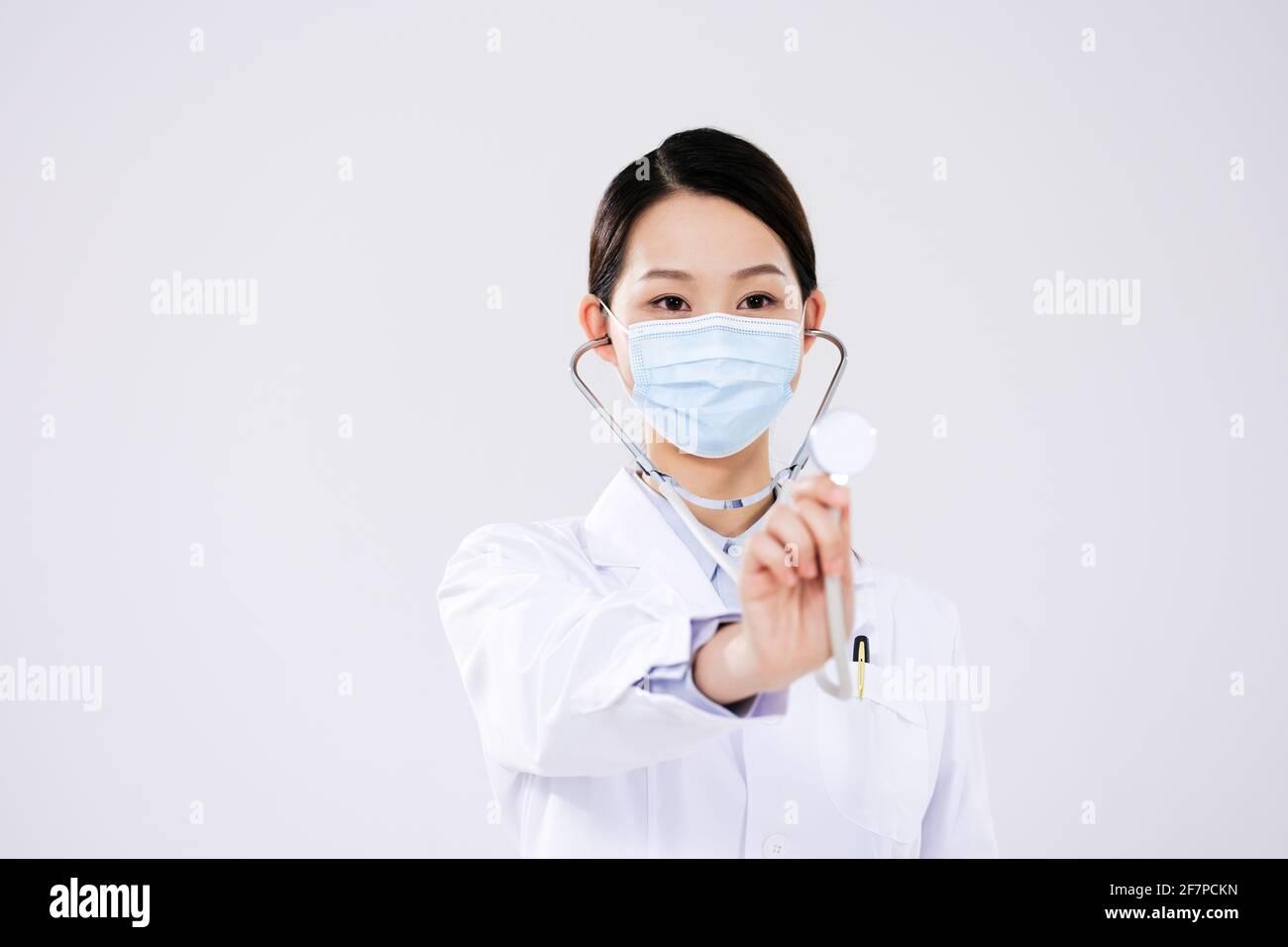 Une femme médecin portant un masque utilise un stéthoscope avant vue Banque D'Images