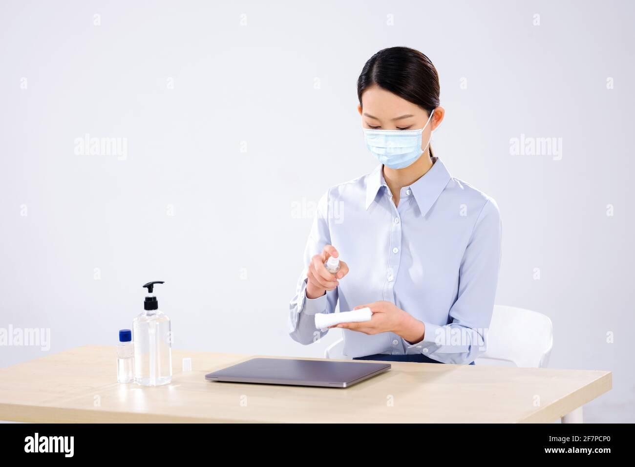 Une femme d'affaires portant un masque essuie son ordinateur avec vue sur le côté alcool Banque D'Images