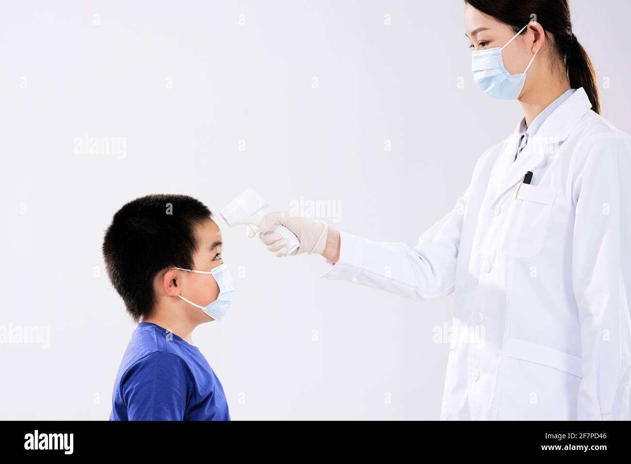 Une femme médecin a pris le visage de température du petit garçon à face Banque D'Images