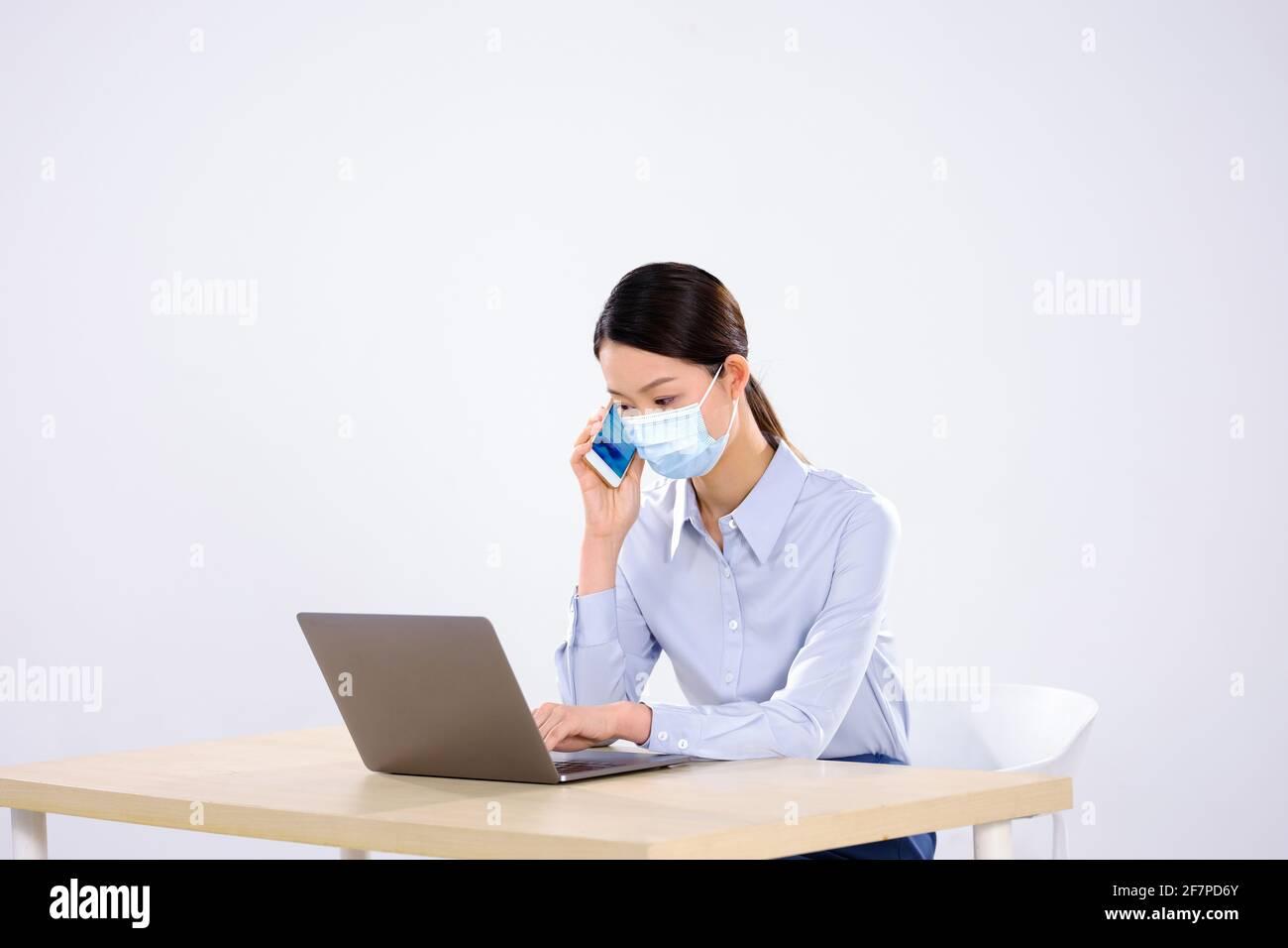 Une jeune femme avec un masque est au téléphone dans la vue latérale du bureau Banque D'Images
