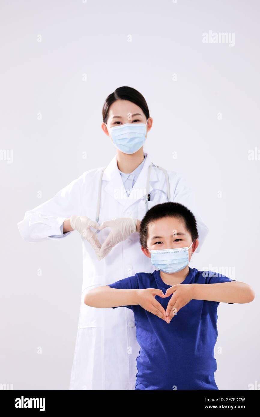 Une femme médecin et un petit garçon ont fait le coeur à mouvements du cœur en regardant la caméra Banque D'Images