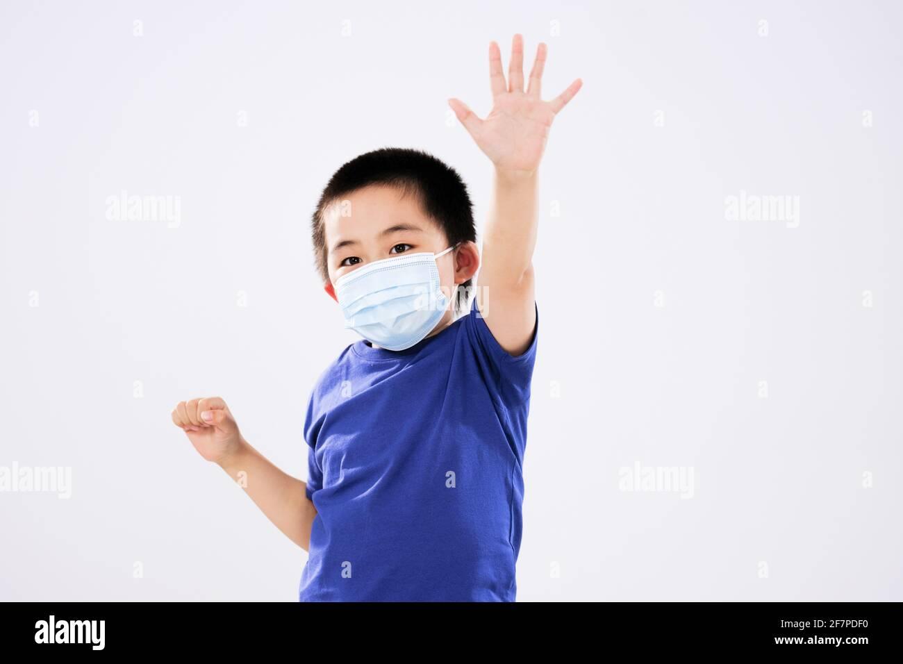 Un petit garçon avec un masque a soulevé son bras non regarder la caméra Banque D'Images
