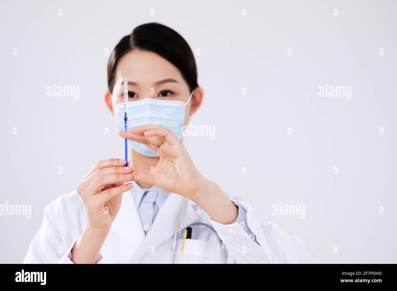 Une femme médecin avec un masque utilise un front de seringue vue Banque D'Images