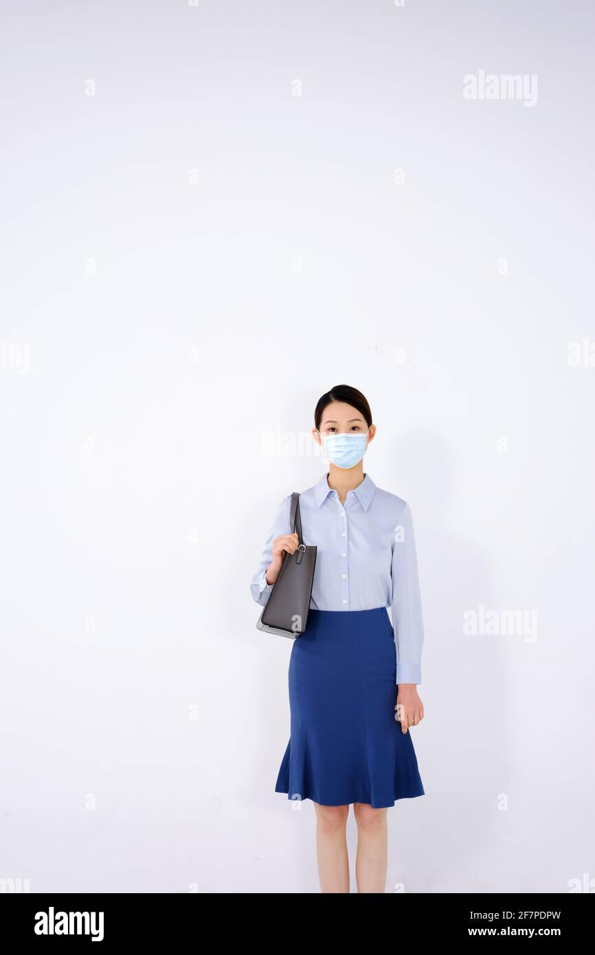 Une jeune femme avec un masque se rend debout Banque D'Images