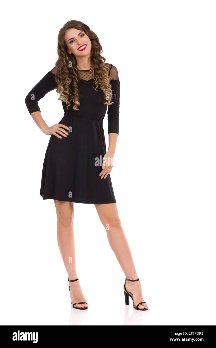 Une jeune femme souriante et détendue, vêtue d'une élégante robe à cocktail noire et de talons hauts, se tient debout et tient les mains sur la hanche. Vue avant. Prise de vue en studio Banque D'Images