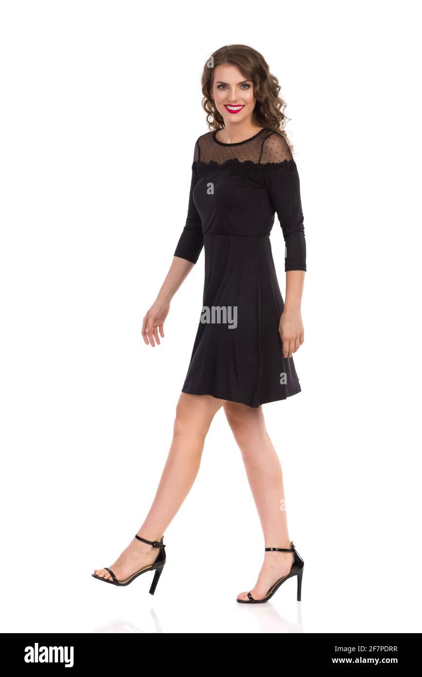 Belle jeune femme en noir élégant robe et talons hauts est de marche et de regarder l'appareil photo et sourire. Vue latérale. Prise de vue en studio pleine longueur isolée Banque D'Images