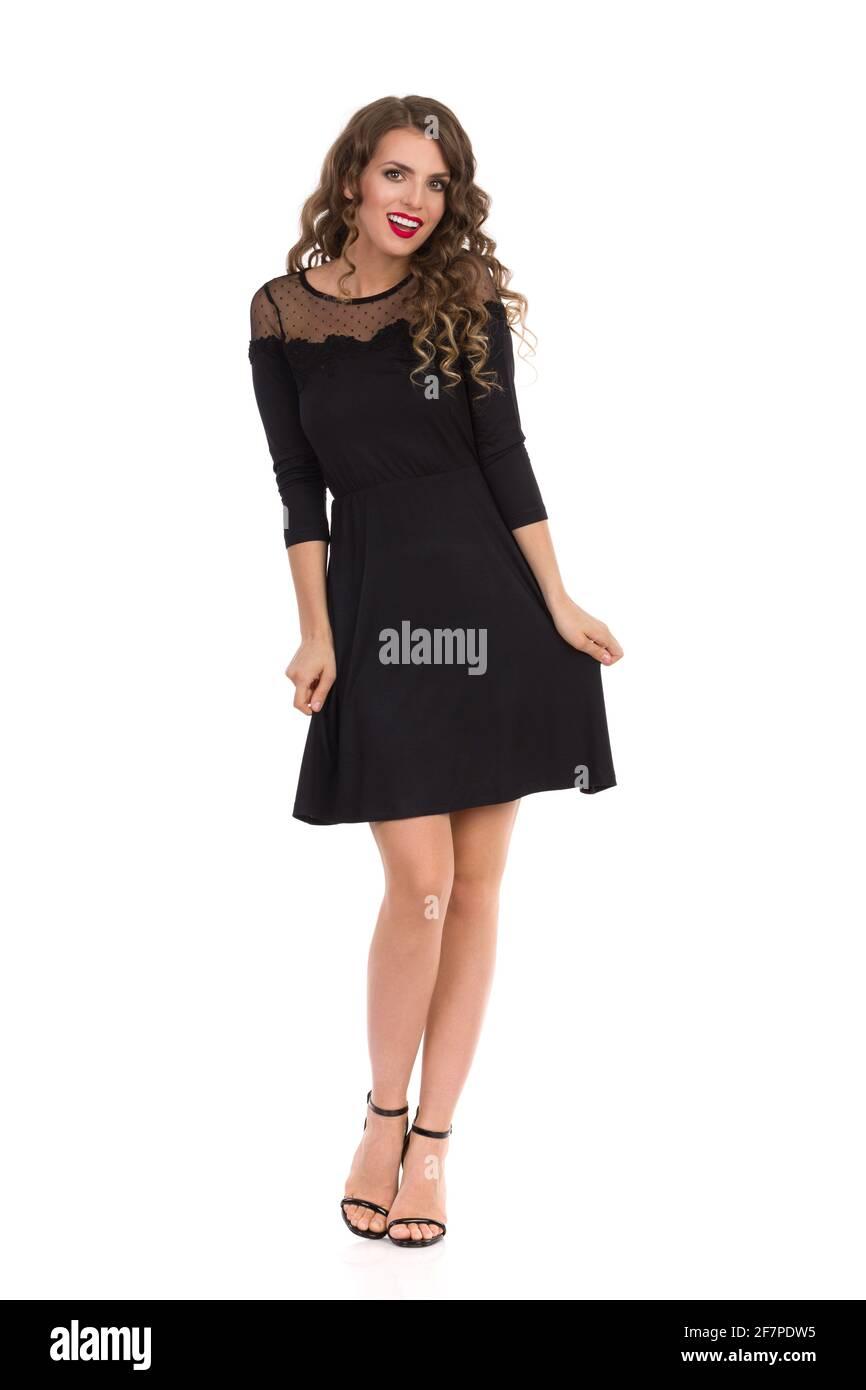 Une jeune femme élégante pose dans une petite robe cocktail noire et des talons hauts. Vue avant. Prise de vue en studio sur toute la longueur isolée sur blanc. Banque D'Images
