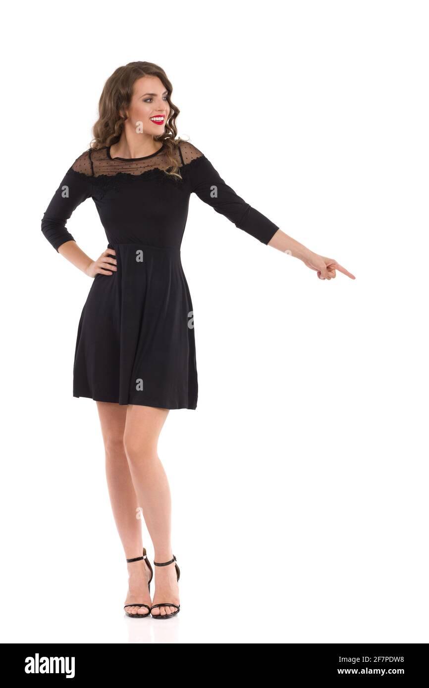Élégante jeune femme en robe de cocktail noire et talons hauts est debout, pointant vers le bas et regardant loin. Vue avant. Prise de vue en studio pleine longueur isolée o Banque D'Images