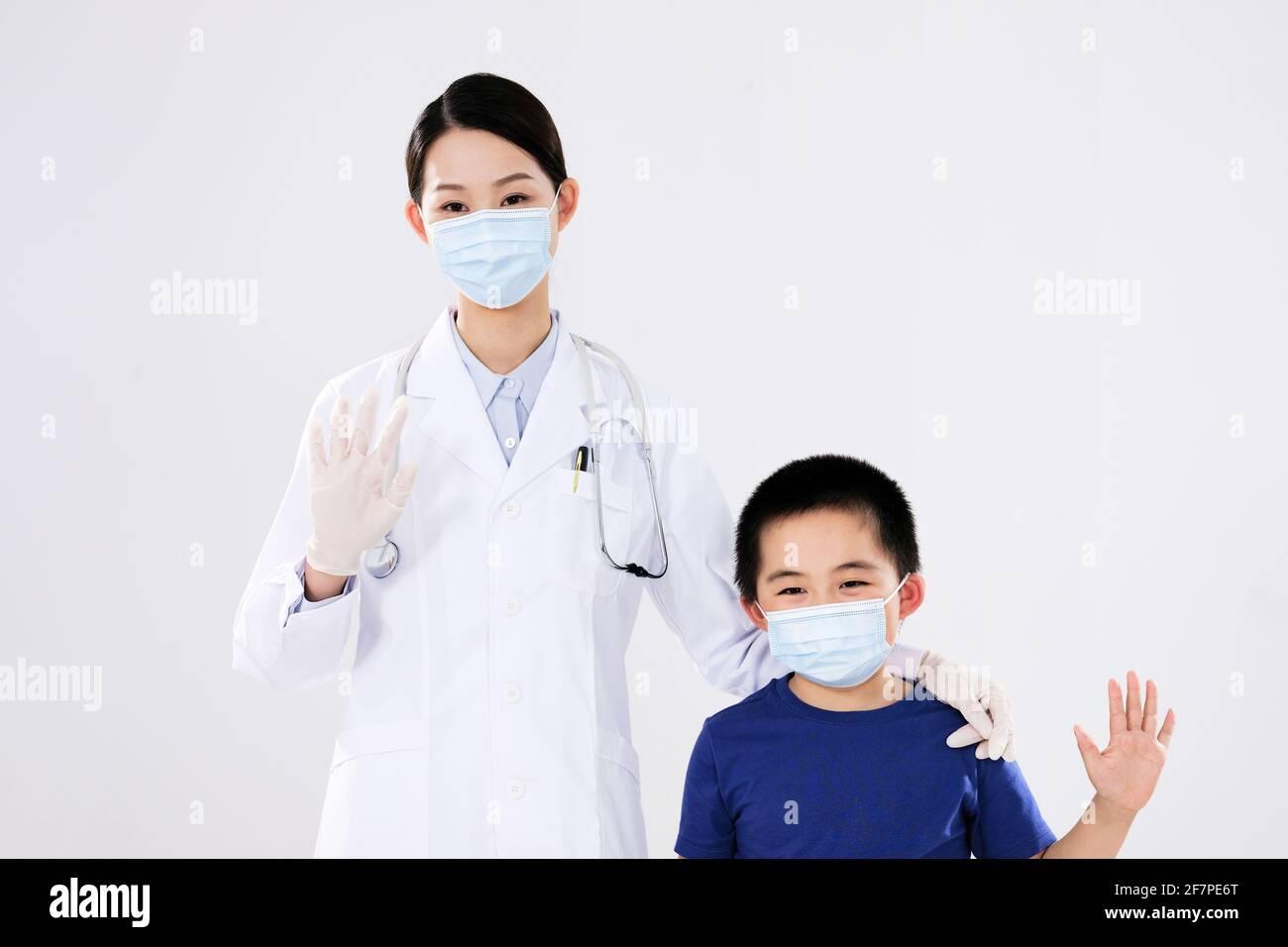 Une femme médecin et un petit garçon agitent en souriant Banque D'Images
