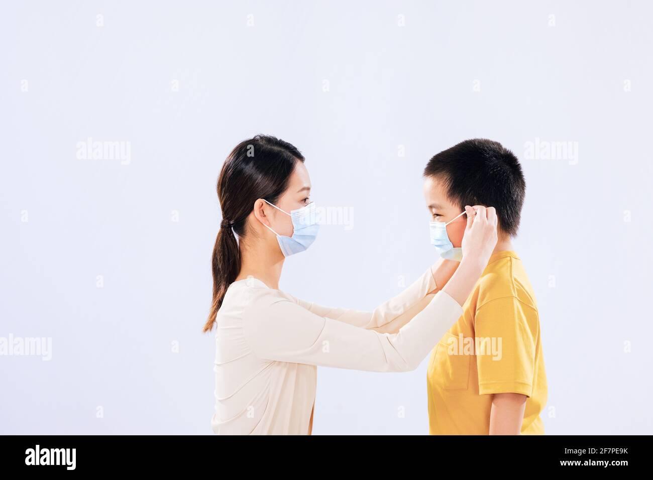 La mère a mis un masque sur le visage du garçon à face Banque D'Images